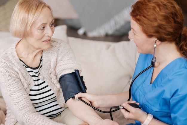 Druckprüfung. fleißige, präzise medizinische mitarbeiterin, die professionelle geräte zum testen und diagnostizieren ihrer älteren patientin verwendet