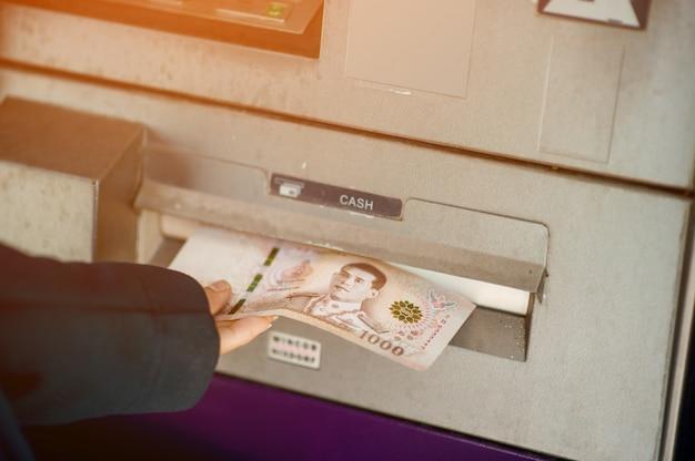 Drücken sie geld in den bankautomaten der bank. finanzgeschäftskonzept mit kopienraum