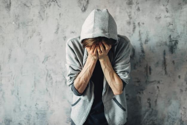 Druggy sitzt auf dem boden, entzugssymptom