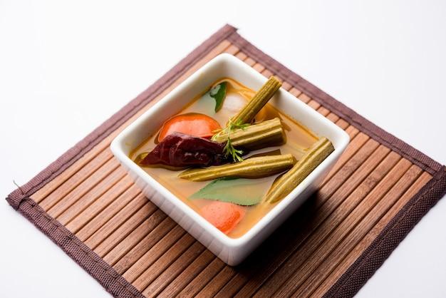 Drumstick curry oder shevga sheng bhaji oder südindischer sambar, serviert in einer schüssel mit stimmungsvollem hintergrund. selektiver fokus