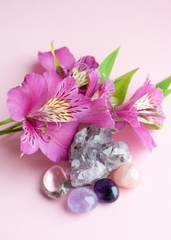 Druse amethyst in form eines herzens, bergkristall, rosenquarz und alstroemeria blüten auf einer rosa oberfläche