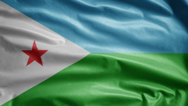 Dschibuti-flagge, die im wind weht. dschibuti schablone weht, weiche und glatte seide. stoff stoff textur fähnrich hintergrund. verwenden sie es für das konzept des nationalfeiertags und der länderanlässe.
