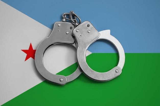Dschibuti flagge und polizei handschellen. das konzept der einhaltung des gesetzes im land und des verbrechensschutzes