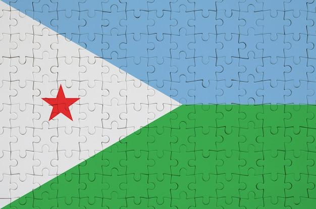 Dschibuti-flagge wird auf einem gefalteten puzzlespiel dargestellt