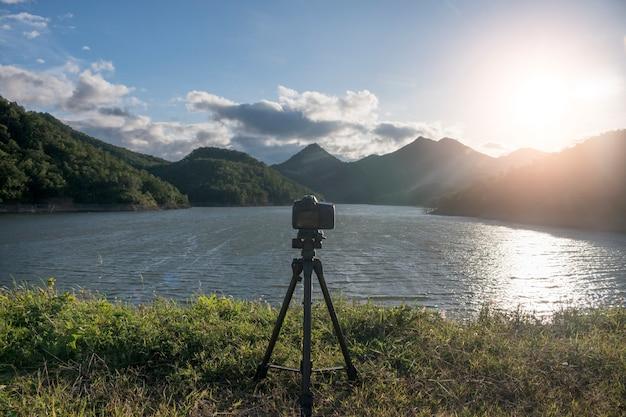 Dslr-kamera auf einem stativ mit dem sonnenaufgang mit see