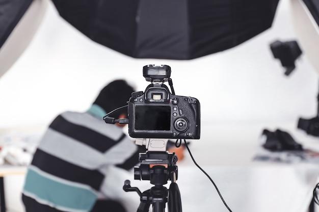 Dslr-kamera und stativ im studio mit einem hintergrund von jemandem, der fotoobjekte anordnet