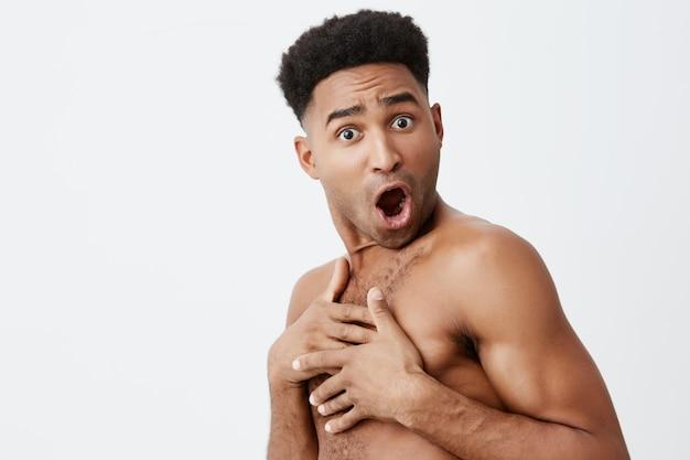 Du hast mich die ganze zeit angeschaut. nahaufnahme porträt von afrikanischen dunkelhäutigen männern mit lockigem dunklem haar ohne kleidung, die sich mit den händen schließt, als jemand plötzlich in den umkleideraum im laden kam.