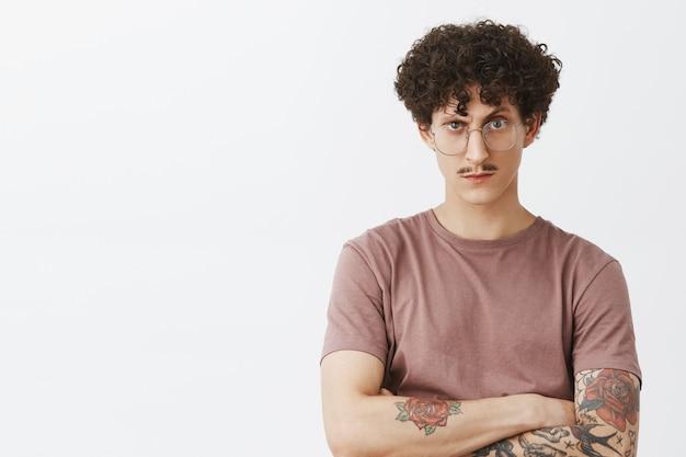 Du kannst ihn nicht austricksen. porträt des intensiven verdächtigen und zweifelhaften stilvollen modernen hipster-kerls mit ausgefallenen schnurrbart-tätowierten armen und lockigem dunklem haar, das unter der stirn zweifelhaft in der brille schaut