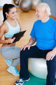 Du machst große fortschritte. selbstbewusster persönlicher trainer, der die zwischenablage hält und lächelt, während er in der nähe eines älteren mannes sitzt