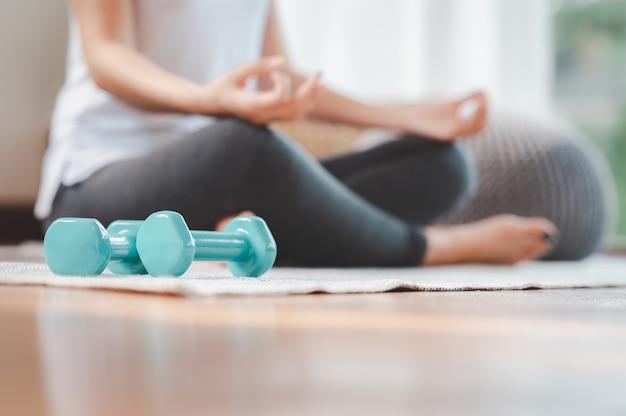 Du mbbell auf dem boden mit frau, die meditation tut
