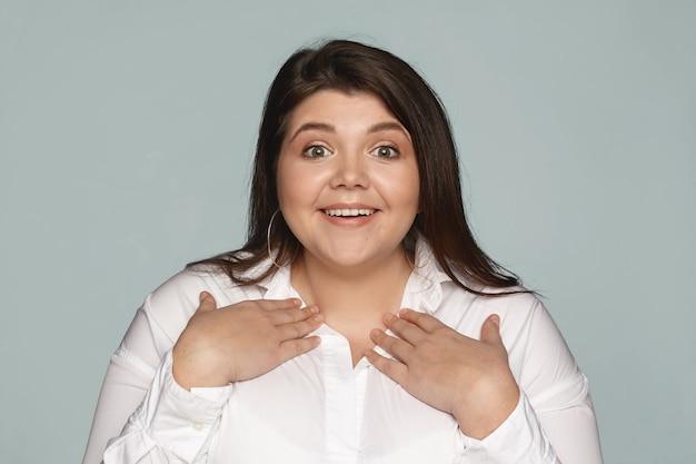 Du meinst mich. faszinierte, verblüffte junge frau in übergröße in weißem hemd, die auf sich selbst zeigt, hände auf der brust hält und breit lächelt, weil sie unter anderen kandidaten für einen positiven job ausgewählt wurde