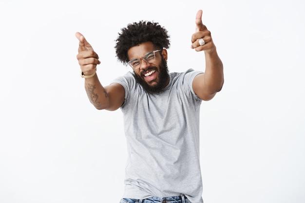 Du rockmann. porträt eines fröhlichen, gut aussehenden, emotionalen, dunkelhäutigen mannes mit afro-frisur und bart, der fingerpistolen auf die kamera zeigt, mit erhobenen händen und breitem lächeln, als er die tanzbewegungen eines freundes mag