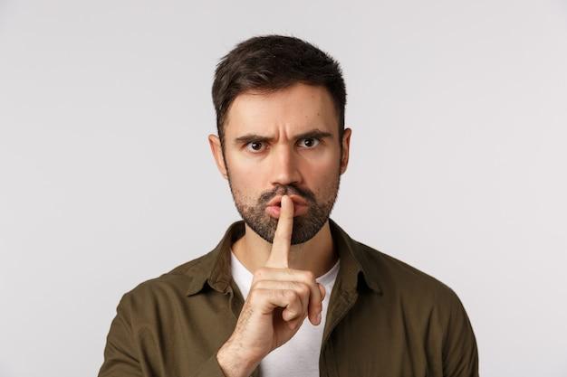 Du solltest lieber schweigen. aggressiver, verärgerter, missfallener kaukasischer bärtiger mann im mantel, schweigen der nachfrage, schweigen mit den zeigefinger-presselippen, die stirn runzelnd gestört, weißer hintergrund