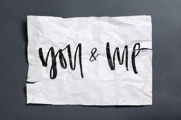 Du und ich. handgeschriebener text auf weißem zerknittertem papier.
