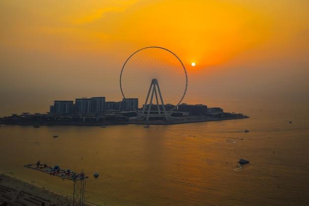 Dubai eye ferris beobachtungsrad während des warmen orange sonnenuntergangs
