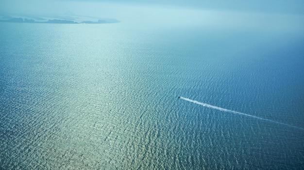 Dubai, luftaufnahme. das boot schwimmt im meer. draufsicht eines weißen bootes, das zum blauen meer segelt.