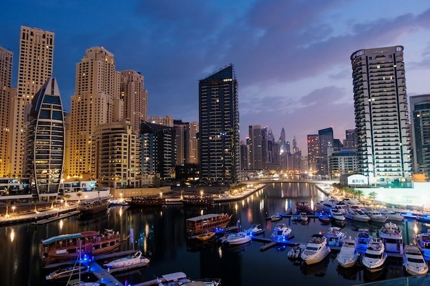 Dubai marina mit booten und gebäuden in der nacht, vereinigte arabische emirate