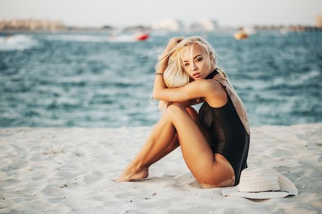 Dubai strand touristische fotografie. russischer emotionaler ady im schwarzen bikini, der sonnenlicht genießt, das blaues wasser des arabischen ozeans übersieht beste abdeckung für magazinkonzept,