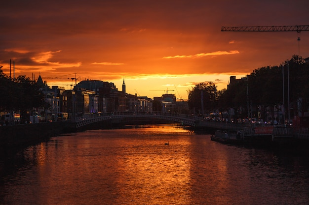 Dublins stadtbild während eines bunten sonnenuntergangs mit wolken und möwen über liffey river