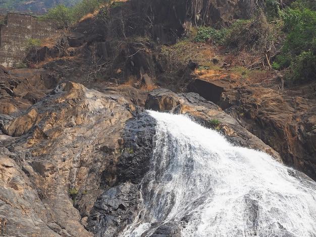 Dudhsagar-wasserfall im indischen bundesstaat goa. einer der höchsten wasserfälle indiens, tief im regenwald gelegen. eine bahn fährt über den wasserfall