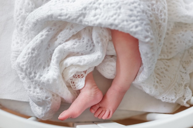 Dünne beine des neugeborenen in einer decke kreisen sie die tagesdecke um die babyfüße ein kind, das mit einer gestrickten spitze bedeckt ist