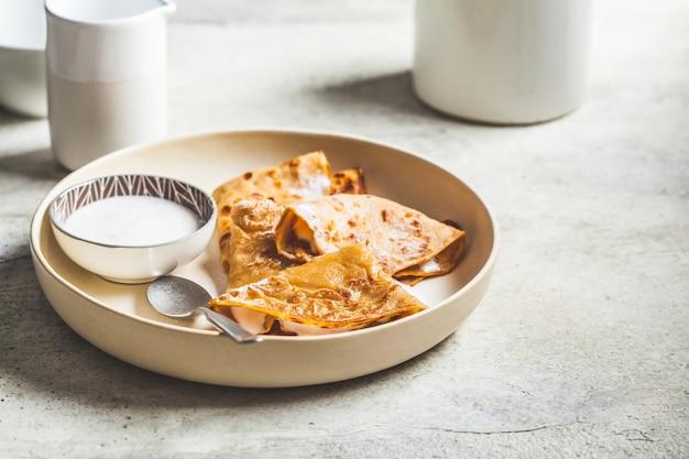 Dünne crêpe-pfannkuchen mit joghurt (saure sahne) auf weißem teller. russisches küchenkonzept.