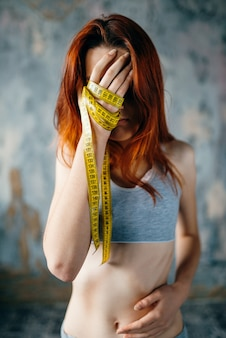 Dünne frau bedeckt ihr gesicht mit händen, die mit maßband gebunden sind. konzept zur fett- oder kalorienverbrennung. gewichtsverlust, magersucht