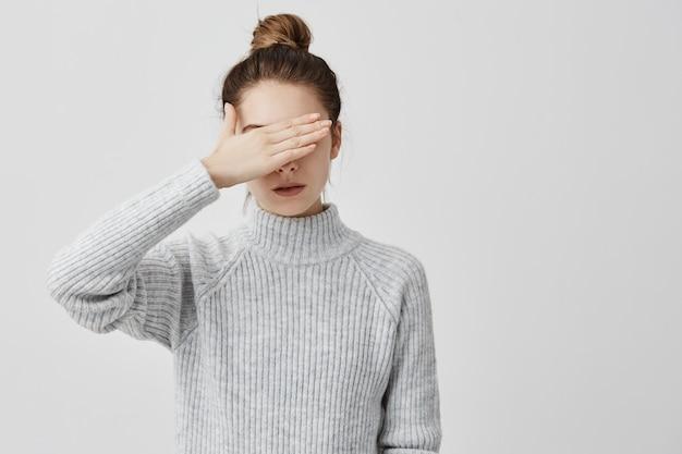 Dünne frau, die graues outfit trägt und ihre augen mit der hand schließt. selbstbewusste frauen, die versuchen, ihr gesicht vor anderen menschen zu verbergen, ziehen es vor, nicht zu sehen. entscheidung, menschliches konzept