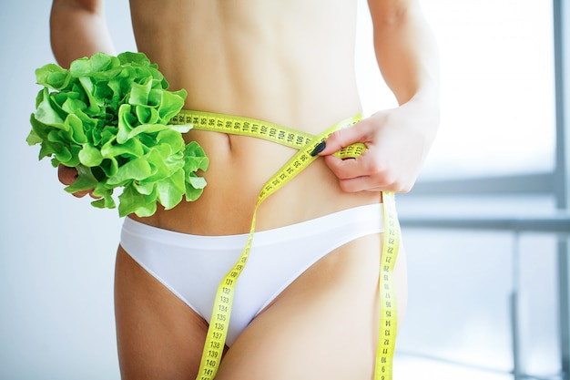 Dünne frau, die im handfrischen grünen salat hält.