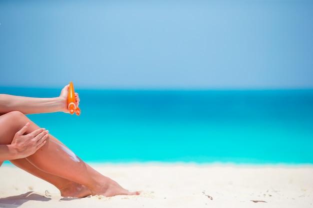 Dünne frau, die lichtschutz auf ihren beinen, sitzend auf sandigem strand mit meer anwendet