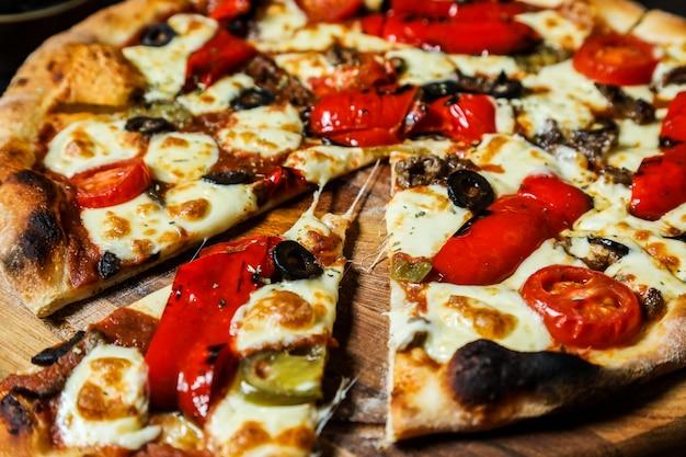 Dünne gemischte pizza mit verschiedenen zutaten nahaufnahme