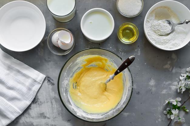 Dünne hausgemachte pfannkuchen. dünnes pfannkuchenrezept. leichte betonoberfläche. draufsicht. schritt für schritt traditionelle pfannkuchen kochen. zutaten. kochen. hände im rahmen