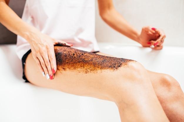 Dünne junge frau in einem hellen seidenpyjama schabt ihr bein, das in einem großen schönen hellen bad sitzt. hautpflege-konzept.