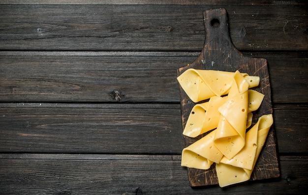 Dünne käsescheiben auf dem schneidebrett. auf einem holz.