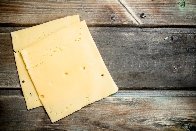 Dünne käsescheiben. auf einem holz.
