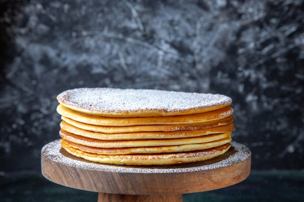 Dünne kuchenschichten der vorderansicht mit zuckerpulver auf dunkler oberfläche des runden holzbretts