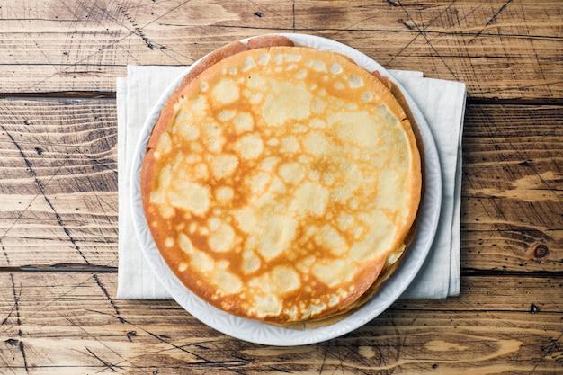 Dünne pfannkuchen auf einem teller. hölzerner hintergrund platz kopieren