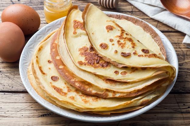 Dünne pfannkuchen auf einem teller. hölzerner hintergrund zutaten zum kochen von eiern, milch, mehl.