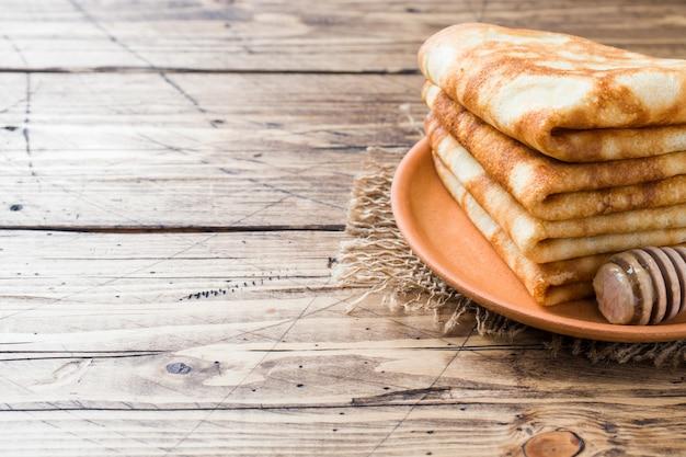Dünne pfannkuchen gestapelt auf einem hölzernen hintergrund. platz kopieren.