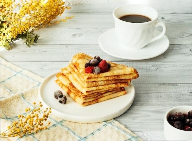 Dünne pfannkuchen mit himbeere und johannisbeere auf teller. russisches traditionelles dessert für fastnachtfeier (maslenitsa).