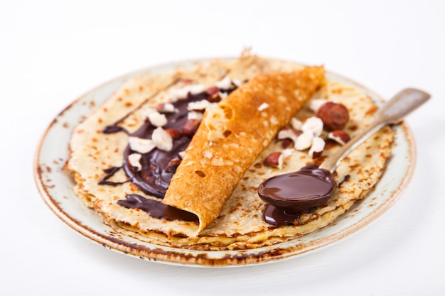 Dünne pfannkuchen mit honig, schokolade, haselnuss