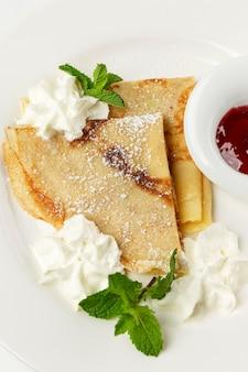 Dünne pfannkuchen mit sahne und beerensauce. traditionelles köstliches gericht. nahaufnahme.