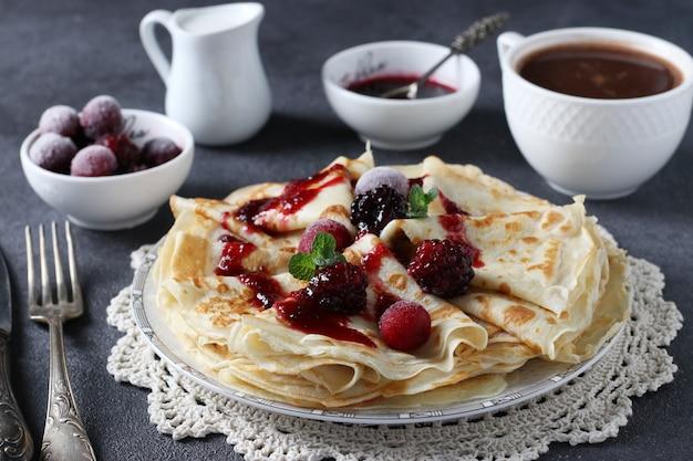 Dünne pfannkuchen mit weizenmehl, eiern und kefir, serviert mit beeren, marmelade und tasse kaffee auf dunkelgrauem tisch. nahaufnahme