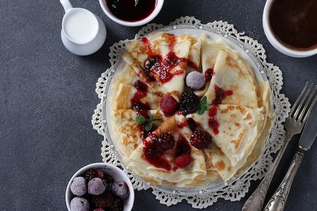 Dünne pfannkuchen mit weizenmehl, eiern und kefir, serviert mit beeren, marmelade und tasse kaffee auf grauem tisch. sicht von oben