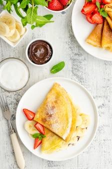 Dünne pfannkuchen oder crepes mit schokoladencreme und banane
