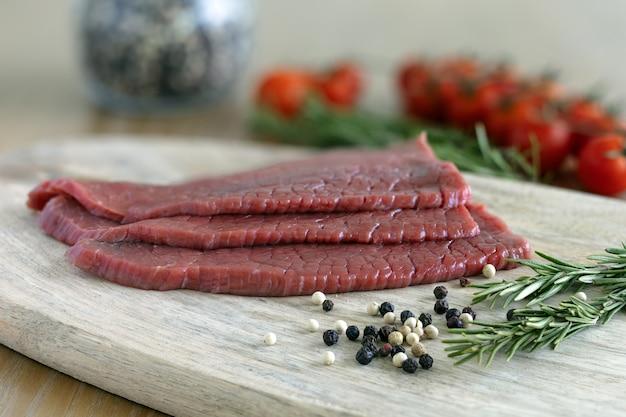 Dünne scheiben mageres rindfleisch auf einem schneidebrett mit pfeffer und rosmarin
