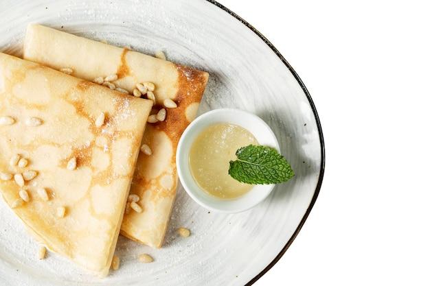 Dünne spitzenpfannkuchen mit honig und nüssen. ein appetitliches traditionelles frühstück der russischen küche. isoliert auf weißem hintergrund. platz für text.