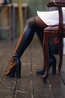 Dünne und sexy weibliche beine, die auf lehnsessel sitzen
