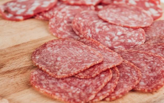 Dünne wurstscheiben auf einem holzbrett kopieren platz. in scheiben geschnittene salami.
