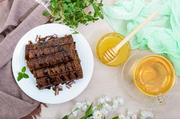 Dünne, zarte schokoladenpfannkuchen, gerollt, auf einem stapel auf einem weißen teller und einer tasse kräutertee mit honig ausgelegt